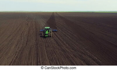 Aerial view of modern tractor cultivating field's soil in...