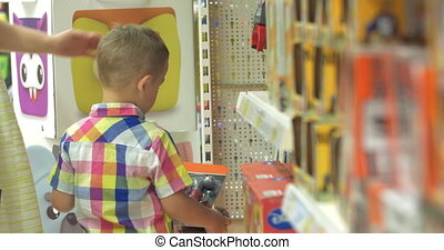 Boy Choosing Toys in the Shop - Little boy is standing in...