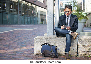 Young asian man looking at mobile phone - Young serious...