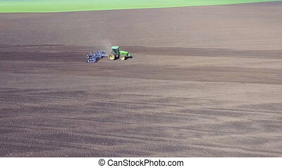 Aerial view of tractor plowing the soil. Top view. Full HD
