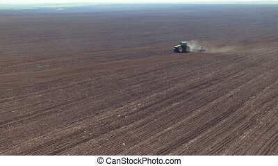 Aerial view of fertile soil, big fields, tractor plowing the...