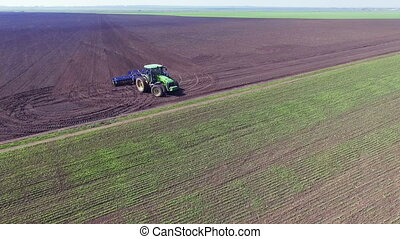 Aerial view of tractor turning around and plowing the soil....