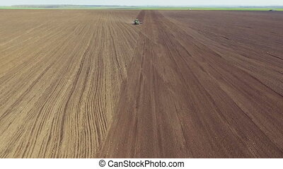 Aerial view of tractor plowing the soil on the field in...