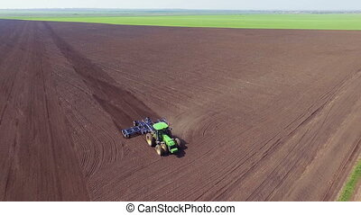 Aerial view of tractor plowing the soil on a big field full...