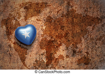 heart with national flag of somalia on a vintage world map...