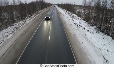 Aerial shot of minivan on winter road - Flying over the...