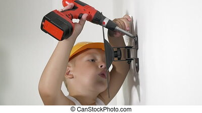 Boy working with electric screwdriver - Close-up of little...