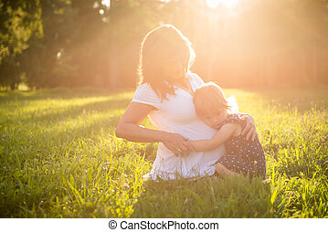 Pregnant woman with child in nature
