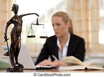 lawyer office - a young lawyer is sitting at her desk in the...