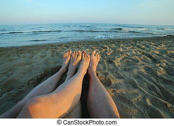 four bare feet of the couple in love on sandy beach