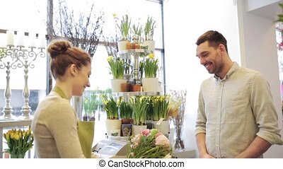 florist woman with flowers and man at flower shop