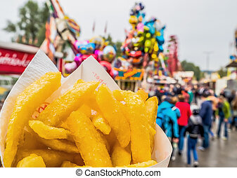 french fries in a bag at a fairground
