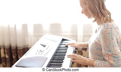 Woman playing a synthesizer - close-up video of a woman...