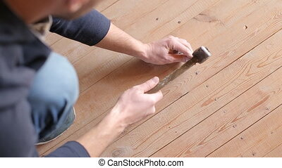 Laying of wooden floor. Close up of driving in nails and...