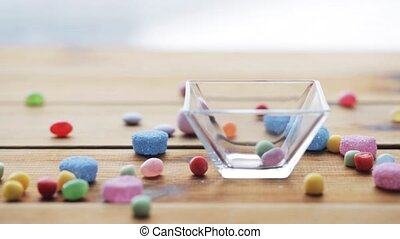 close up of hand dropping jelly candies to bowl - food,...
