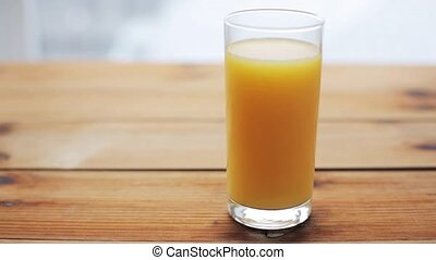 full glass of orange juice on wooden table - healthy eating,...