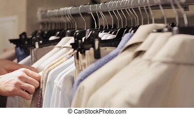 man choosing clothes in clothing store - sale, shopping,...