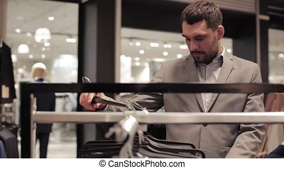 young man choosing suit in clothing store or mall - sale,...