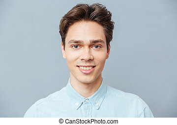 Smiling man looking at camera over gray background
