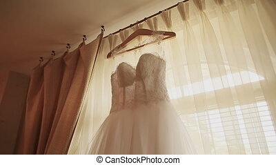 Beautiful white luxury wedding dress on hanger on the background of a window