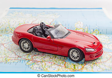 Red toy car on the open old road atlas