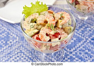 Salad with shrimp and tomatoes in glass on linen tablecloth