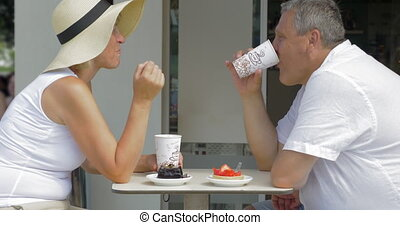Senior couple having desserts and coffee in cafe - Mature...