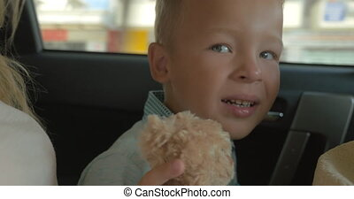 Boy with Plush Toy on the Car Back Seat - Closeup shot of a...