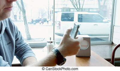 Man texting and browsing with mobile app in a cafe - Man...