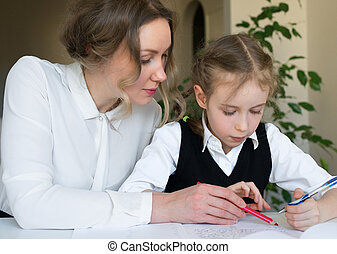 Mother helping daughter with homework at home.
