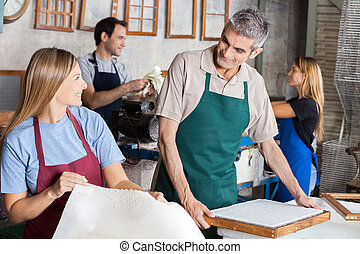 Workers Making Papers While Looking At Each Other