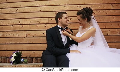 Bride touches a butterfly the groom and sit on a bench in...