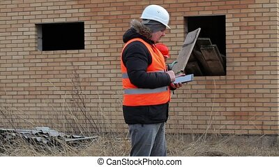 Site manager using tablet PC and worker sorting boards