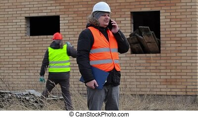 Site manager with smart phone and worker with sledgehammer...