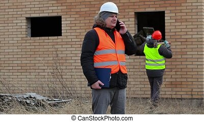 Site manager talking on smart phone and worker with...