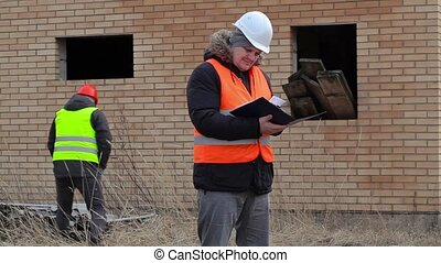 Site manager with documentation and worker in background...