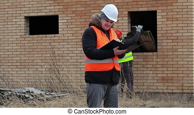 Site manager checking documentation and worker in background...