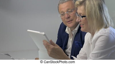Businesspeople Working with Tablet - Mature businesspeople...