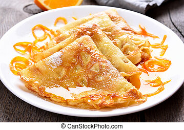 Delicious crepes with orange syrup, close up view