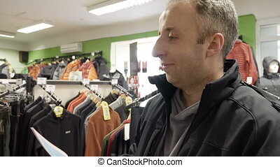 Man shopping clothes chooses and tries on gloves