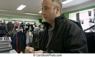 Man shopping for clothes and speaks to cashier - Man...