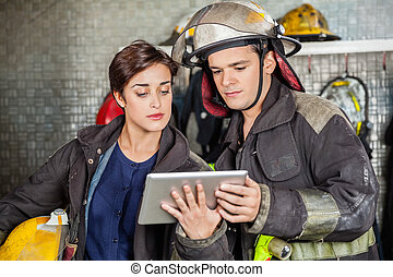 Firefighters Using Digital Tablet - Young firefighters using...