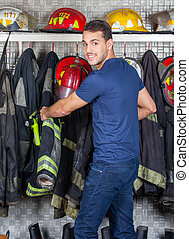 Smiling Worker Removing Uniform Hanging At Fire Station -...