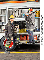Happy Firefighters Standing By Truck At Fire Station