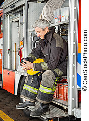 Smiling Fireman Looking At Coffee Mug While In Truck -...