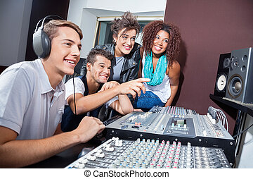 Multiethnic Musicians Mixing Audio Together At Table