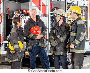 Confident Firefighter Standing With Team Against Truck -...