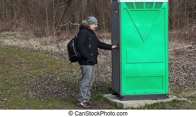 Man waiting near green portable toilet in the park
