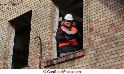 Site manager checking documentation in building's second...