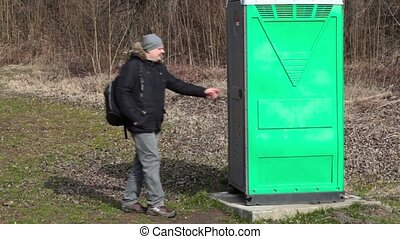 Man go in green portable toilet - Man go to in green...